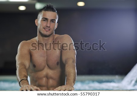 young healthy good looking macho man model athlete at hotel indoor pool - stock photo