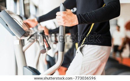 Young healthy group of people working out on a elliptic trainer