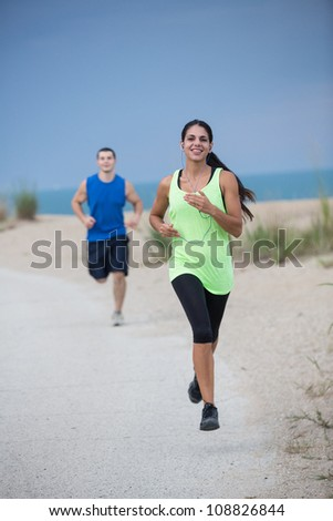 Young Healthy Looking Couple Jogging Outdoor by Beach under Summer Sky