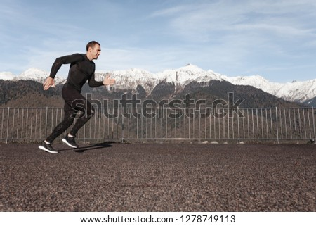 Young healthy male runner in a black suit makes a jog on the nature against the backdrop of snow-capped mountains. Fitness and jogging concept #1278749113
