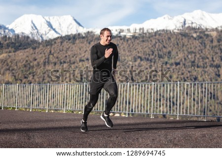Young healthy male triathlete in a black suit makes a jog on the nature against the backdrop of snow-capped mountains. Fitness and jogging concept #1289694745