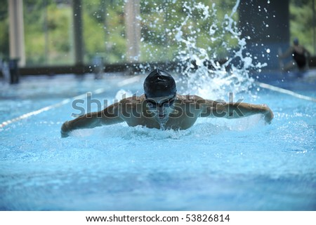 young healthy man with muscular body swims in swimming pool and representing healthy and recreation concept