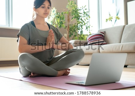 Young healthy mindful indian woman wear sportswear meditate namaste hands watch online class tutorial on laptop at home doing yoga training fitness workout sport exercise feel stress free sit on mat.