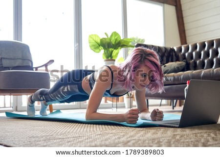 Young healthy sporty fit woman with pink hair wear sportswear doing plank sport training exercise watching online class tutorial on laptop at home. Online fitness workout video virtual coach concept.
