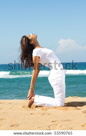 young healthy woman doing yoga on beach