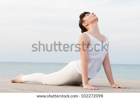 Young healthy woman doing yoga position at sea: Cobra pose