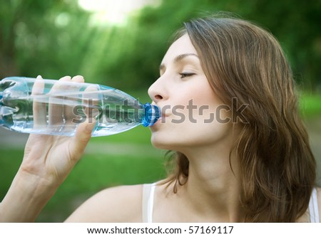 Young healthy woman drinks water from bottle.Outdoor
