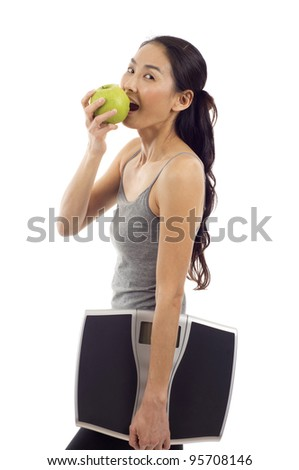 Young healthy woman eating an apple and carrying a digital weight scale isolated over white background
