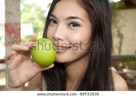 Young healthy woman holding green apple - stock photo