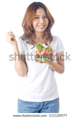Young healthy woman holding vegetable salad in plastic bowl with fork on white background