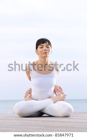 Young healthy woman meditating and exercising with yoga poses: Lotus pose