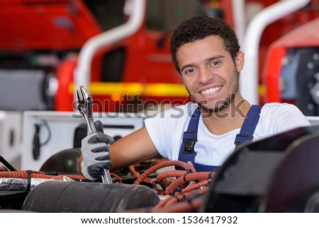 young heavy equipment mechanic smiling