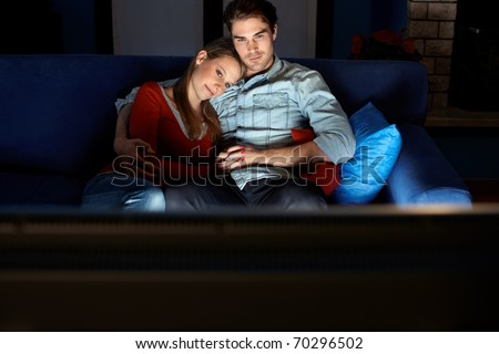 young heterosexual couple hugging on sofa and watching movie on tv at home. Horizontal shape, front view, copy space