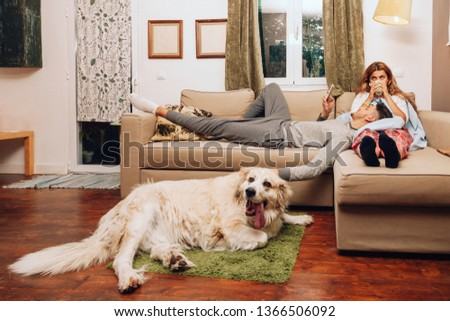 Young heterosexual couple together on sofa with their dog using smartphone and drinking from a cup #1366506092