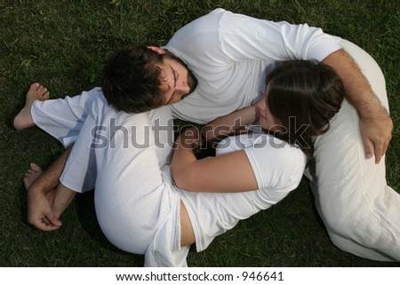 Young heterosexual lovers, laid on the grass, in a ying yang pose. They complement each other.