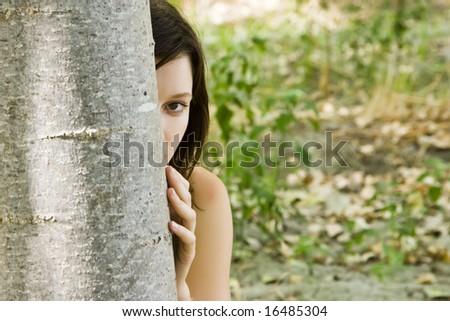 Young hidden woman staring at camera.