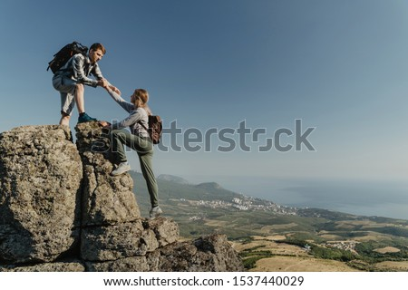 Young hiker an holding a woman hand helps to climb to the top of the mountain. The concept of help and support. Motivation for success