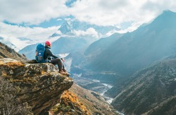 Young hiker backpacker female sitting on the cliff edge and enjoying Ama Dablam 6,812m peak view during Everest Base Camp (EBC) trekking route near Phortse, Nepal. Active vacations concept image