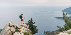 Young hiker backpacker man using trekking poles enjoying the Mediterranean Sea on clifftop during Lycian Way trekking walk. Famous Likya Yolu Turkish route near Letoon. Active vacations concept image