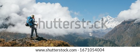 Young hiker backpacker woman using trekking poles enjoying the Nuptse 7861m mountain during high altitude Acclimatization walk. Everest Base Camp trekking route, Nepal. Active vacations concept image