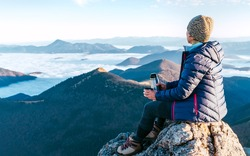 Young hiker female sitting on the mountain summit cliff and enjoying mountains valley covered with clouds view. Successful summit climbing concept image.