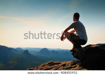 Young hiker in black pants and shirt  is sitting on cliff\'s edge and looking to misty hilly valley bellow