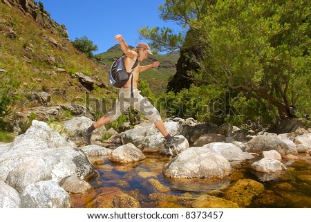 Young hiker jumps across small river in awesome mountains. Shot in the Kromrivier - Du Toitskloof Nature Reserve, near Paarl, Western Cape, South Africa.