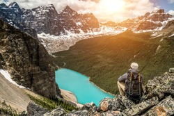 Young hiker man enjoying Moraine Lake landscape from surrounding mountain top. Banff National Park, Alberta, Canada. Beautiful turquoise waters in high view with Rocky Mountains peaks during sunset.