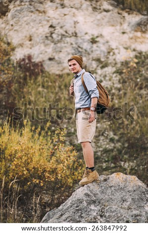 Young hiker man opening his backpack on nature on a halt resting. Hiking and recreation theme
