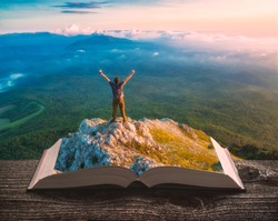 Young hiker man standing on a cliff above the mountain valley on the pages of an open magical book. Majestic landscape. Travel and education concept.