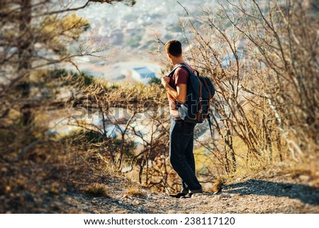 Young hiker man with backpack looking back in autumn outdoor in highlands. Hiking and recreation theme