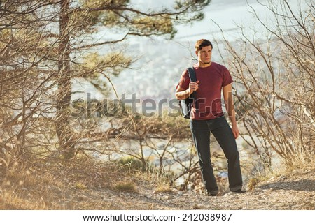 Young hiker man with backpack walking in forest. Hiking and recreation theme