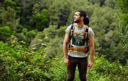 Young hiker with backpack look around while planning mountain walk trip, man hiker get lost in beautiful green forest and looking to laterally copy space area for your text message or information