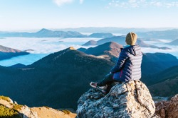 Young hiker woman sitting on the mountain summit cliff and enjoying mountains valley covered with clouds view. Successful summit climbing concept image.