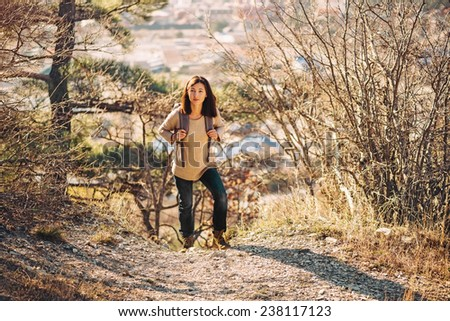 Young hiker woman with backpack trekking in autumn outdoor in highlands. Hiking and recreation theme