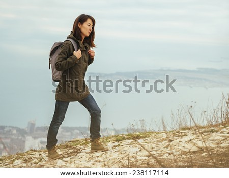 Young hiker woman with backpack walking in highlands on background of sea. Hiking and recreation theme
