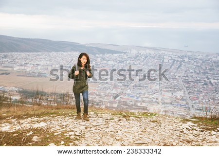 Young hiker woman with backpack walking in highlands over the city. Hiking and recreation theme