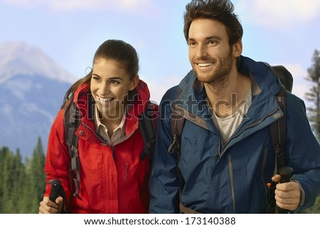 Young hiking couple trekking in mountains, climbing uphill, smiling.
