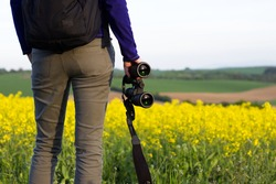 Young hiking woman watching landscape with binoculars. Tourist girl in rape field at countryside. Binoculars in a female hand.