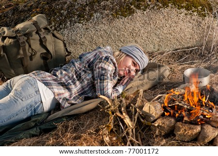 Young hiking woman with backpack sleep by campfire countryside