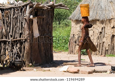 Young Himba woman carries a bucket of water on her head in the middle of the himba village.