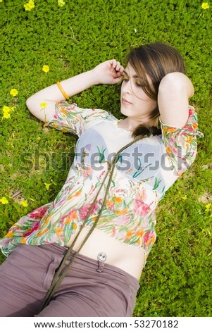 stock photo : young hippie girl lying in the flowers with happy face tattoo