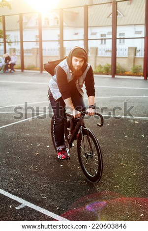 young hipster bearded handsome man riding sport style fixed gear bicycle in autumn urban style street neighborhood