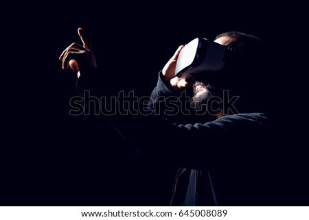 Young hipster bearded man wearing virtual reality goggles. Black background studio VR concept