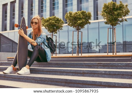 Young hipster blonde girl in casual clothes and sunglasses, sitting on steps against a skyscraper, resting after riding on the skateboard.