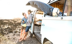 Young hipster couple at relax moment together by oldtimer mini van - Travel lifestyle concept with indie people on minivan adventure trip having fun with mobile smart phone - Warm sunshine filter