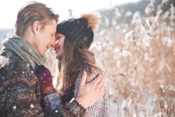 Young hipster couple hugging each other in winter park. Love story, a beautiful stylish young boyfriend and girlfriend.