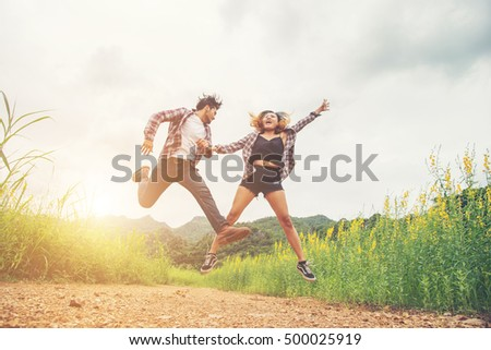 Young hipster couple in love outdoor jumping at yellow flower field with mountain sunset background. Jump up high enjoying freedom and enjoy. #500025919
