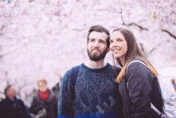 Young hipster couple portrait in Stockholm with cherry blossoms at Kungstradgarden, the swedish for Kings Garden. Love and friendship concepts with a hipster theme.