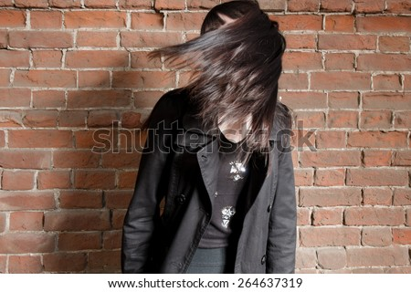 Young hipster gil shake her hairs against red brick wall with copyspace, dishevelled street fashion look #264637319
